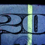 Detail of fluorescent strip and fluorescent fibers in a US $20 bill